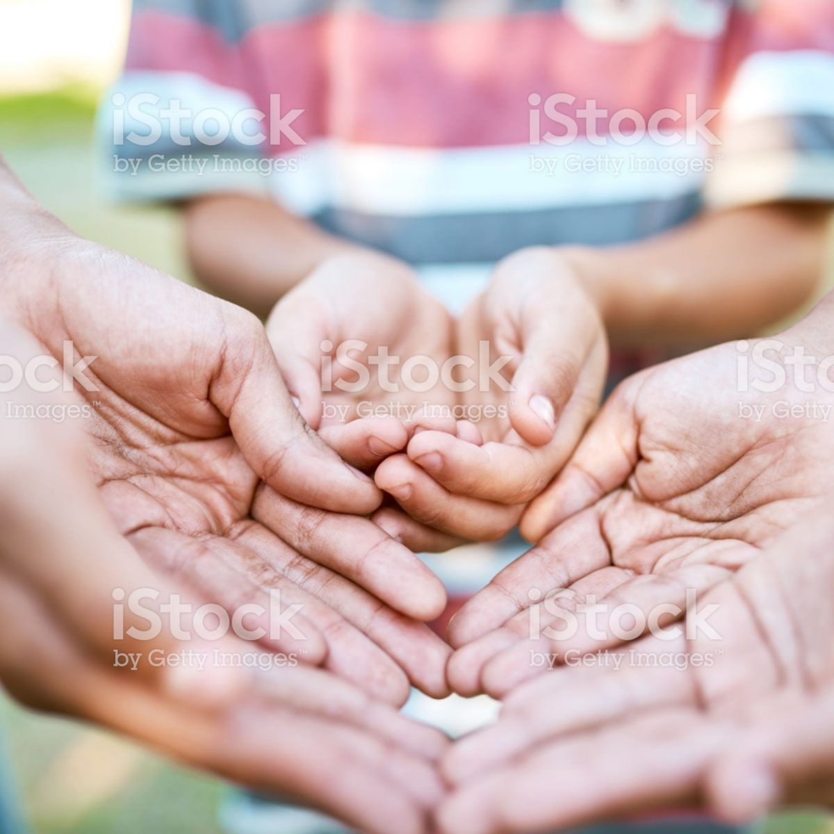 Cropped shot of a group of children with their hands cupped outdoors